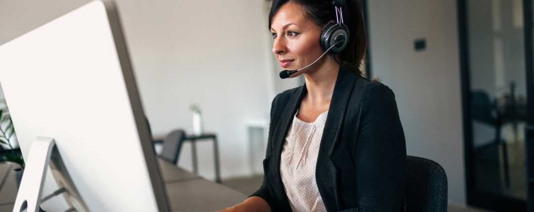 Businesswoman working with headset on computer
